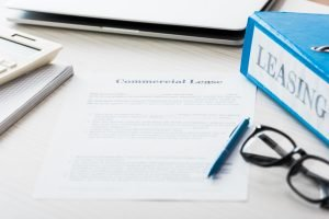 Retail commercial leasing rules and regulations listed in a binder on a desk with a pen, glasses and contract symbolizing commercial leasing.