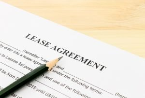 Lease Agreement Contract Document and Pencil Bottom Left Corner on Wood Table. Legal document for business event