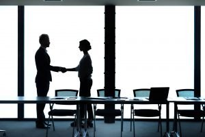 Business handshake of businessman and businesswoman. Concept of teamwork and partnership