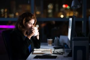 Business woman sitting at her work desk at night drinking coffee and staring at a computer screen symbolizing that she is working overtime.