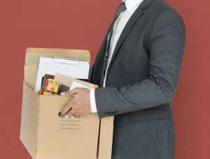 Businessman holding box of desk items symbolizing a temporary layoff due to Coronavirus.
