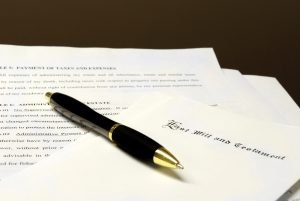 Image of a pen laying on top of papers that are a last will and testament for Estate Planning.