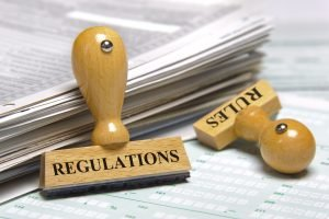 "Image of a stack of papers and rubber stamps marked with ""Regulations"" and ""rules"" symbolizing land use and zoning laws."