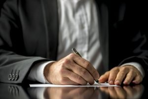Conceptual image of a man signing a last will and testament document.