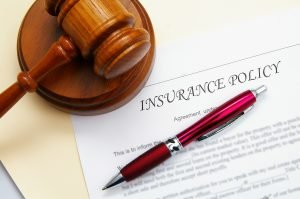 Image of an insurance policy paperwork with a pen and a gavel.