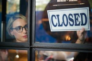 "Attractive young woman inside a shop with her face in the window flipping over a ""closed"" sign symbolizing a shut down of business due to the pandemic."