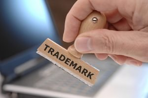 "Image of a person's hand holding a rubber stamp that says ""Trademark"" representing protecting you business through trademark law."