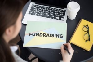 "Woman sitting at a desk looking down at a paper that says ""fundraising"" with laptop and coffee representing nonprofit legal issues."