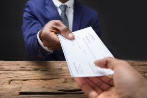 Close-up Of A Businessman's Hand Giving Check To Someone Over Wooden Desk Representing Counterfeit Check