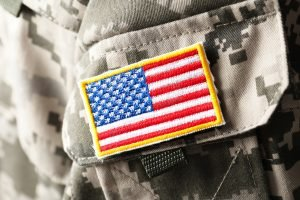 Closeup of the shoulder of a U.S army uniform with small American flag patch.