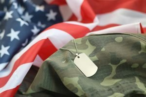 Silvery military beads with dog tag on United States fabric flag and camouflage uniform. Army token on USA banner close up symbolizing military law.