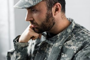 Man in military fatigues looking sad resting hand on chin.