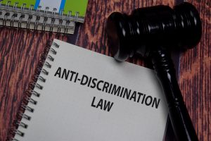 Anti-discrimination law tablet with gavel on desk