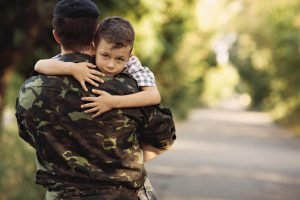 Man in fatigues holding a small boy signifying military divorce law.
