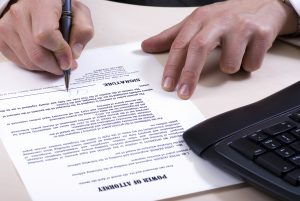 A man is signing a power of attorney, focus is on the tip of the pen.