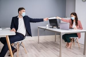 Man and a woman at an office working with masks on and social distancing.
