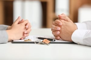 Couple's hands placed on either side of a lawyer's desk representing division of marital assets in a divorce.