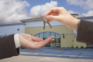 Agent handing over keys to empty commercial building representing a commercial lease.