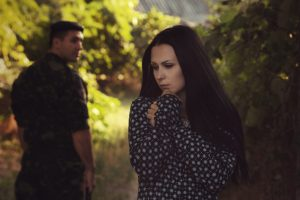 Image of a military man looking over his shoulder at his spouse who is cowering symbolizing military domestic violence.