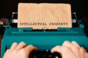 """Image of hands typing """"Intellectual Property"""" on a teal typewriter representing IP law or Intellectual Property lawyers."""